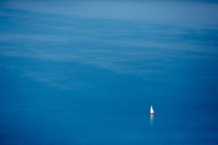 Rotes Schiff Mit Weissen Segeln auf Blauem Wasser