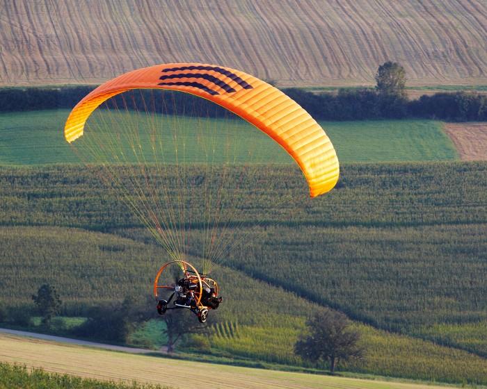 Motorschirmtrike Xcitor in orange über Wiesen und Feldern In Nähe Des Donautals