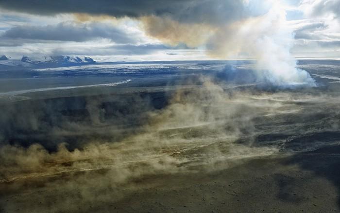 Spalte die Lava Spuckt Und Fliessende, glühende Lava. aus der entfernung dahinter der Gletscher Und davor ein Sandsturm