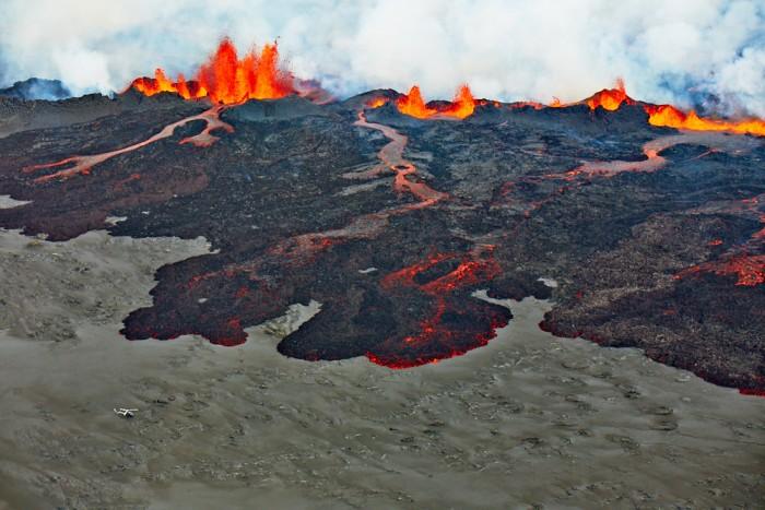 Spalte die Lava Spuckt Und Fliessende, glühende Lava. Links Unten im Bild ein Helikopter Und drei Personen